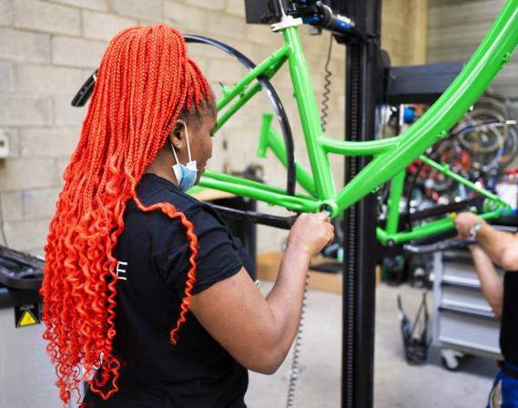 Une femme répare un vélo dans un atelier free Vélov