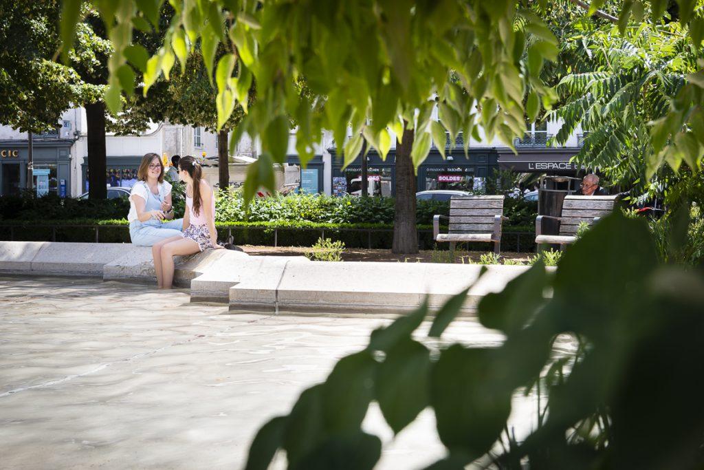 Une place à Lyon avec des espaces ombragés procurés par les arbres