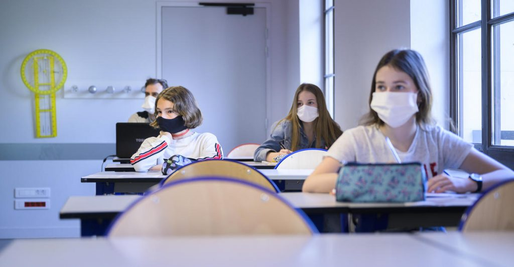dans une classes des collégiens et des collégiennes respectent les distances physiques et portent des masques