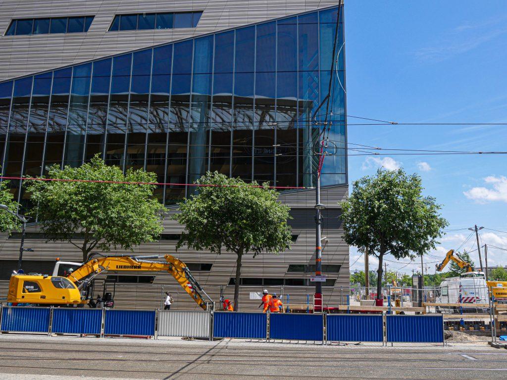 une pelle et des barrières de chantier devant l'hotel de région